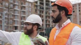 Der Erbauer- und Architektenmann besprechen den Bauplan des modernen Geschäftszentrums, das nahe steht stock video footage