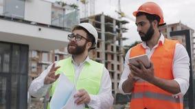 Der Erbauer- und Architektenmann besprechen den Bauplan des modernen Geschäftszentrums nahe gehend stock footage