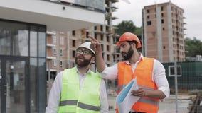 Der Erbauer- und Architektenmann besprechen den Bauplan des modernen Geschäftszentrums nahe gehend stock video