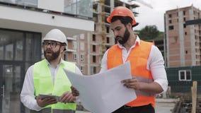 Der Erbauer- und Architektenmann besprechen den Bauplan des modernen Geschäftszentrums nahe gehend stock video footage