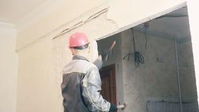 Der Erbauer zerstört den Gips auf der Wand stock video footage