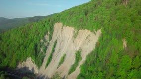 Der Erdrutsch auf dem Fluss Luftbrummen-Gesamtlängen-Ansicht: Flug über Frühlingsbergdorf mit Wald im Sonnenaufgang weich stock video