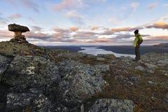 Der erfüllte männliche Wanderer, der den Sonnenuntergang genießt, färbte Landschaft, nachdem er zur Gebirgsspitze riskiert hatte Lizenzfreie Stockfotos