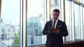 Der erfüllte Mann steht am Fenster und benutzt seine Tablette stock video footage