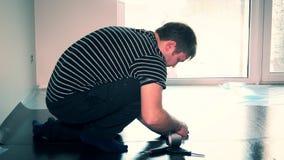Der erfahrene Mann, der hinunter Bodenbelag aufnimmt, lag mit schottischem zugrunde stock video footage