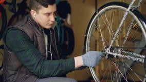 Der erfahrene Mechaniker dreht Fahrradfelge Mechanismus überprüfend und Pedal beim Reparieren des Fahrrades drehend Berufszyklus stock video