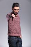 Der ernste junge Modemann, der den Daumen gestikulieren zeigt unten Stockfotografie
