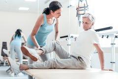 Der ernste Trainer, der altes verkrüppelt ausdehnt, bemannt Beine stockbilder