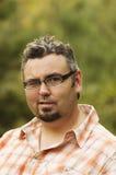 Der erwachsene kaukasische Mann, der Gläser trägt, blinzelt in Kamera mit natur Lizenzfreie Stockbilder