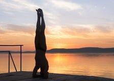 Der erwachsene Mann, der Yoga tut, trainiert bei Sonnenuntergang, Kopfstand Stockfotos