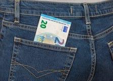 Der Euro der Banknote 20, der aus den hinteren Jeans heraus haftet, stecken ein Stockfoto