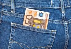 Der Euro der Banknote 50, der aus den Jeans heraus haftet, stecken ein Stockbild