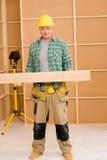 Der fällige Heimwerkertischler tragen hölzernen Lichtstrahl Lizenzfreies Stockfoto