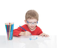 Der fünfjährige Junge in den blauen Punkten sitzt an einem weißen Tisch und und zeichnet Bleistifte Lizenzfreies Stockfoto
