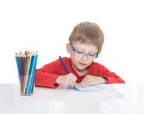Der fünfjährige Junge in den blauen Punkten sitzt an einem weißen Tisch und und zeichnet Bleistifte Stockbild