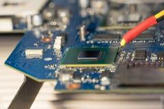 Der Fachmann leitet Reparaturlaptop-Motherboardpläne Ersatzchipgrafikkarte auf der lötenden Infrarotstation Foto der Motherboardr stockfoto