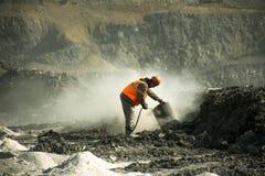 Der Fahrer der Bohrmaschine säubert den Filter vom Staub in der Kohlengrube stockfotos