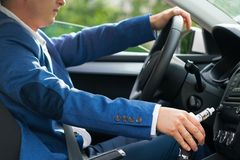 Der Fahrer des Autos sitzt hinter dem Rad und hält in seiner Hand eine elektronische Zigarette stockbild