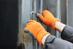 Der Fahrer des LKWs in den orange Arbeitshandschuhen, Sand und Züge geholt die Leiter auf dem Körper zwecks öffnen stockbild