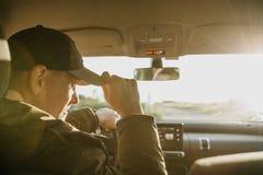 Der Fahrer oder der Tourist innerhalb des Autos justiert die Baseballmütze stockbilder