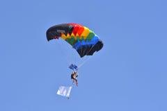 Der Fallschirmspringer mit einem mehrfarbigen Fallschirm fliegt in den Himmel Lizenzfreies Stockbild