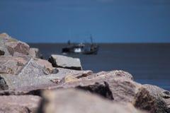 Der Felsen, das Meer, das Boot und der Himmel stockfotografie
