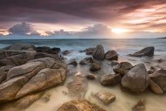 Der Felsen und das Meer in der Farbe der Sonnenuntergangzeit Lizenzfreie Stockfotos