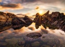 Der Felsen und die Reflexion von kalim setzen mit Sonnendurchbruch auf den Strand Lizenzfreies Stockfoto