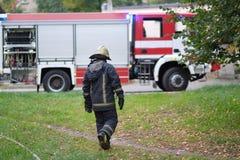 Der Feuerwehrmann geht zum Löschfahrzeug Stockbild