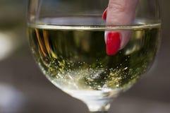 Der Finger der Frau mit rotem Nagel im Weinglas Stockbilder