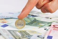 Der Finger des Mannes, der eine Euromünze auf Eurobanknoten hält Stockfotografie