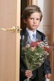 Der First-grader mit einem Blumenstrauß Stockfotografie