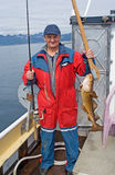 Der Fischer auf dem Boot nahe der Insel Skrova Lizenzfreies Stockfoto