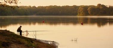 Der Fischer fängt auf dem See an der Dämmerung stockfotos
