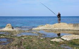 Der Fischer fischt auf dem Ufer des Mittelmeeres Stockbilder