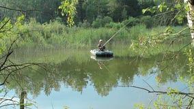 Der Fischer schwimmt auf den Fluss in einem aufblasbaren Boot Bewegliche Kamera durch Schieber Tätigkeiten im wilden stock video footage