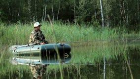 Der Fischer schwimmt auf den Fluss in einem aufblasbaren Boot Bewegliche Kamera durch Schieber Tätigkeiten im wilden stock footage