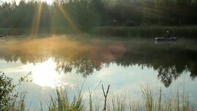 Der Fischer schwimmt auf den Fluss in einem aufblasbaren Boot Die Strahlen der Sonne spielen im Rahmen Tätigkeiten im wilden stock video
