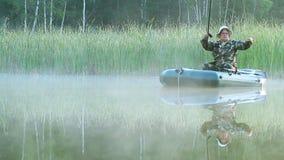 Der Fischer schwimmt auf einen See auf einem aufblasbaren Boot mit einer Angelrute Früher Morgen mit Nebel auf dem Wasser ferien stock video footage