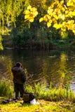 Der Fischer steht auf dem Ufer des Sees im Herbst stockbilder