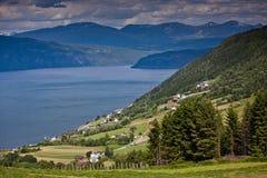 Der Fjord und das Dorf von der Höhe des Sommers in Norwegen Lizenzfreie Stockfotos