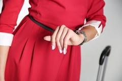 Der Flugbegleiter betrachtet ihre Uhrnahaufnahme lizenzfreie stockfotos