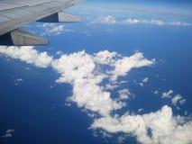 Der Flugzeugflügel über dem blauen bewölkten Himmel Lizenzfreies Stockfoto