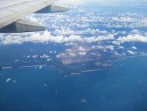 Der Flugzeugflügel über dem blauen Ozean Lizenzfreies Stockfoto