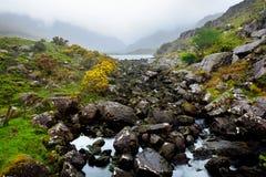 Der Fluss Loe und schmaler Gebirgspassstraßenwind durch das steile Tal Gaps von Dunloe, Grafschaft Kerry, Irland Lizenzfreie Stockbilder