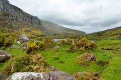 Der Fluss Loe und schmaler Gebirgspassstraßenwind durch das steile Tal Gaps von Dunloe, Grafschaft Kerry, Irland Stockbilder