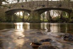 Der Fluss Teign gleitet unter einer alten Steinaußenseite Chagford der brücke gerade in Devon, England stockbilder