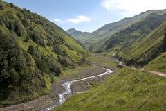 Der Fluss, der zwischen die Berge über dem Durchlauf auf der Straße hinaus zu Shatili fließt Stockbild