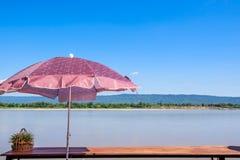 An der Flussansicht in blauen Himmel des ruhigen Sommers, in Wind, in Sonnenschein und in bunten Regenschirm Lizenzfreie Stockfotos