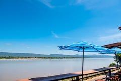 An der Flussansicht in blauen Himmel des ruhigen Sommers, in Wind, in Sonnenschein und in bunten Regenschirm Lizenzfreie Stockbilder
